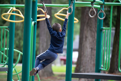Image of boy swinging on monkey bars