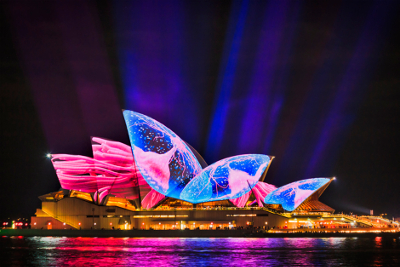 Image of the sails of the Sydney Opera House illuminated in electric blues and pinks.