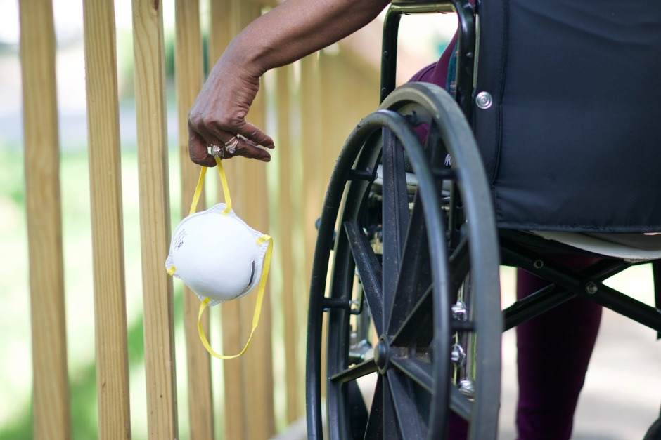 wheelchair user holding a surgical mask