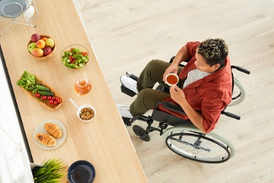 healthy food and woman in wheelchair drinking tea