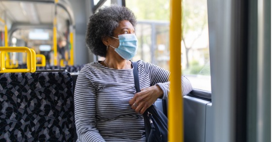 woman on bus wearing surgical face mask