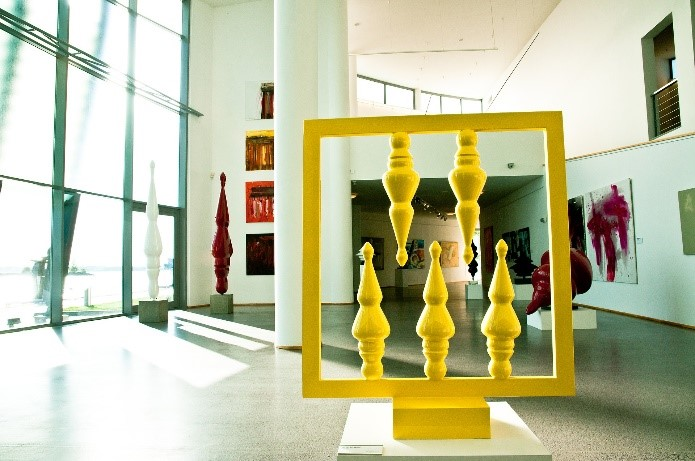 Art gallery featuring a yellow art exhibit displayed in the middle of the floor. Other exhibits are hung on the walls and surrounding areas