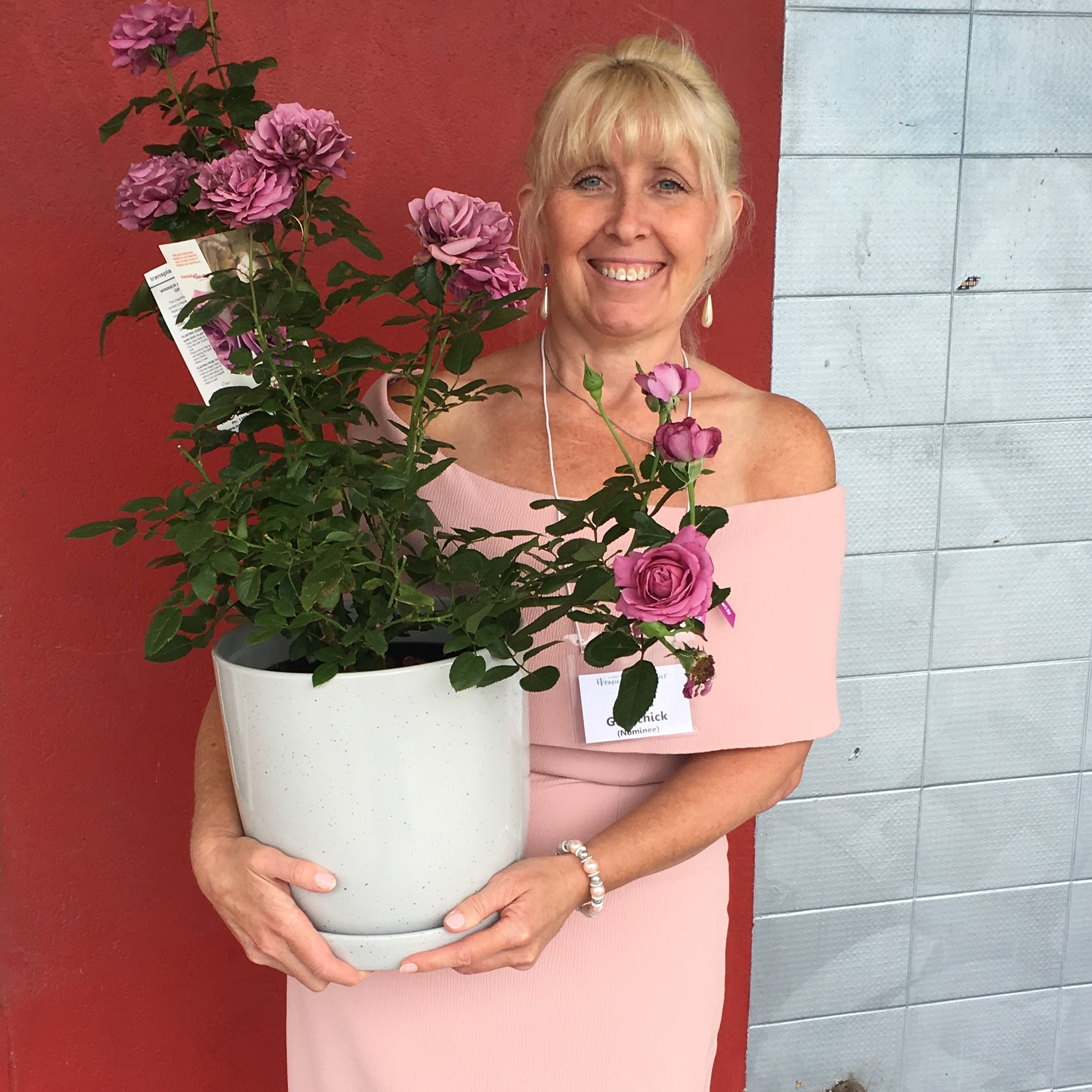 A well dressed woman is holding a potted rose