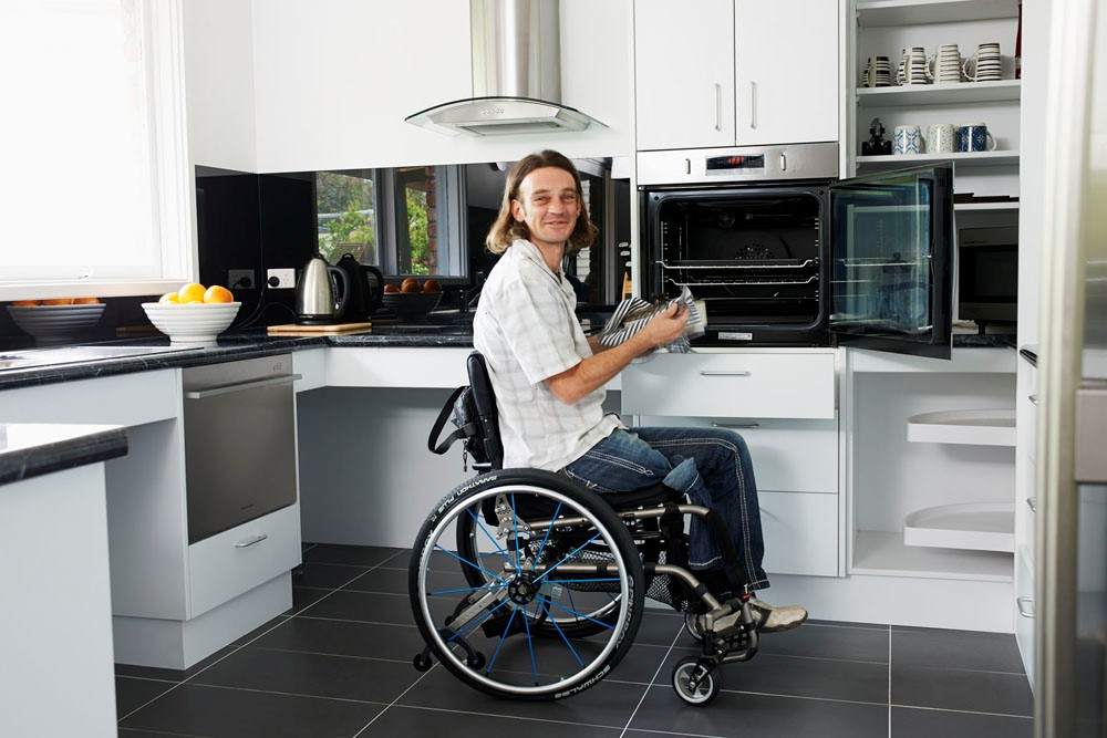 Modified kitchen that includes accessible appliances and wheelchair accessible worktops.