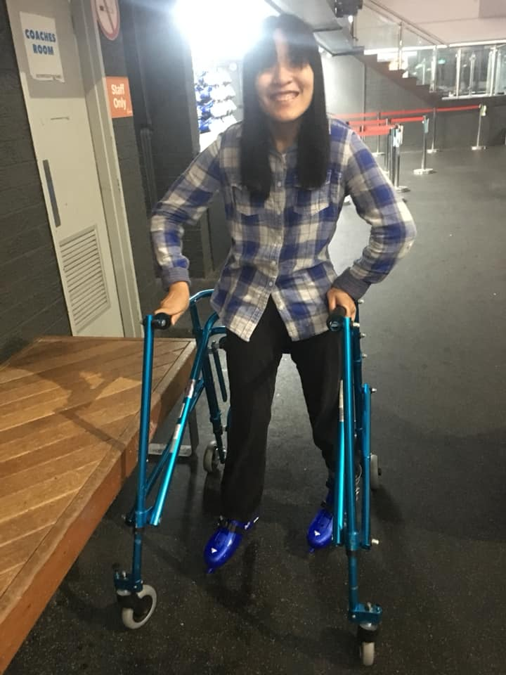 Nicole skating on an ice rink with a mobility aid to support her.