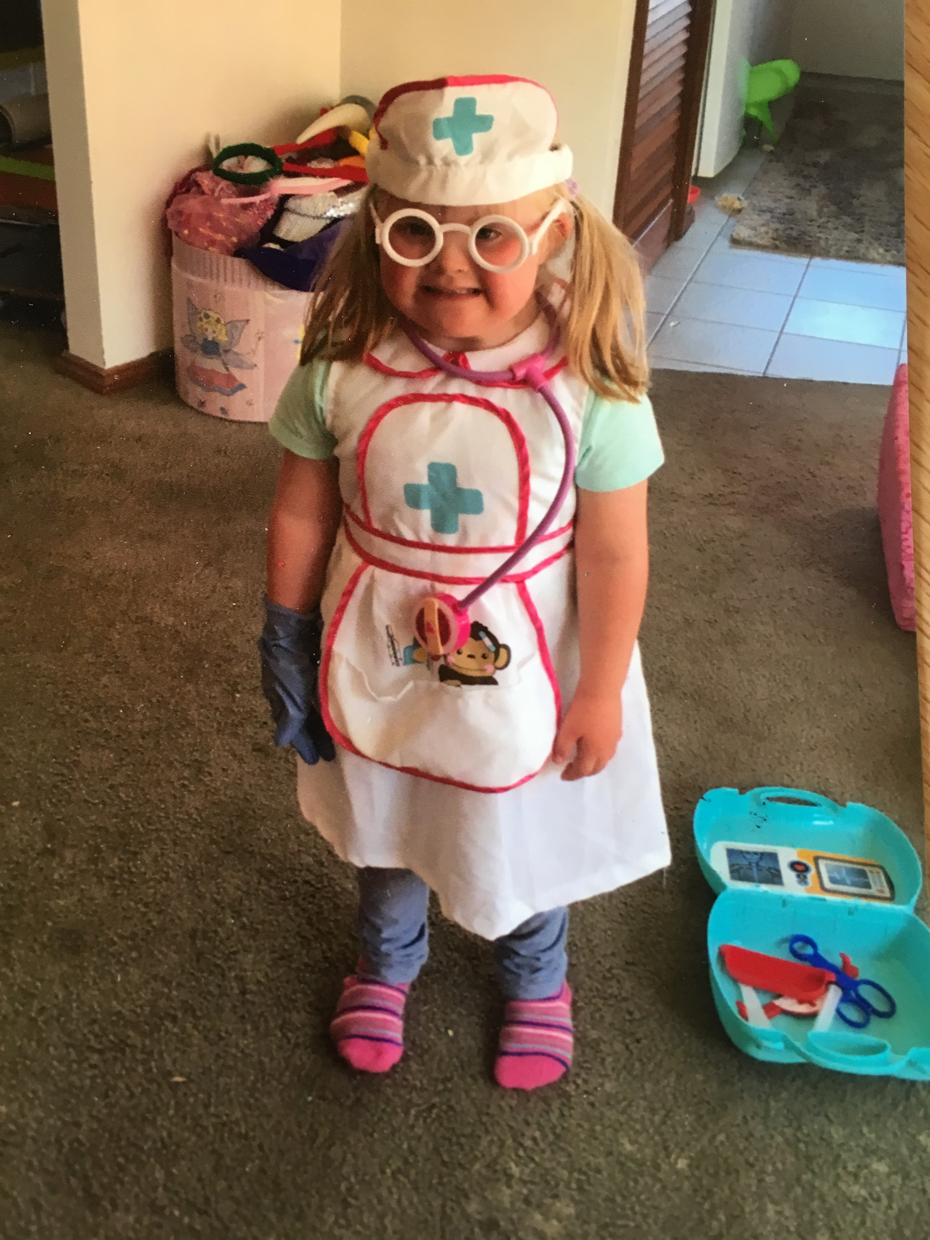 A small child is dressed as a nurse in a uniform with brightly coloured accessories