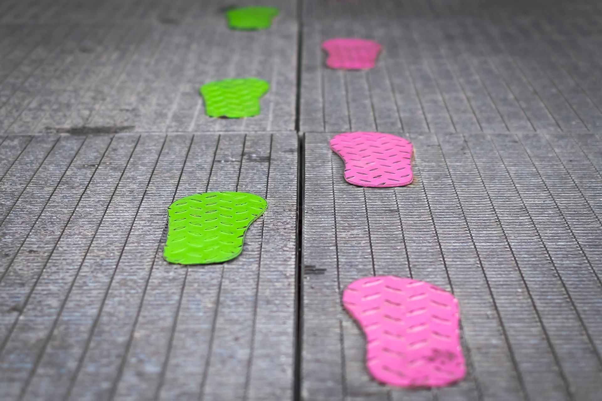 Image displays pink and green coloured footsteps depicting taking steps