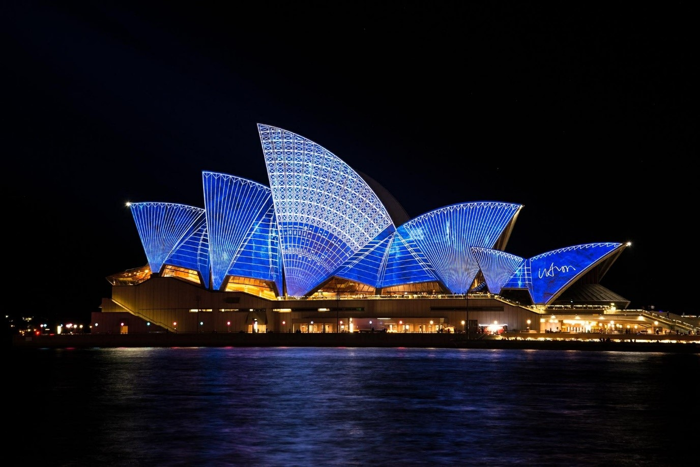 A panoramic view of Sydney Opera House lit up in patterned blue lights