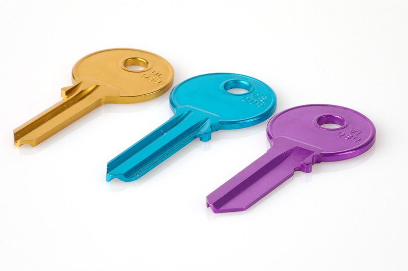Three coloured keys laying on a white background