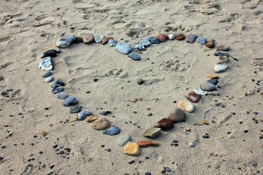 Heart shape made out of stones and resting in the sand