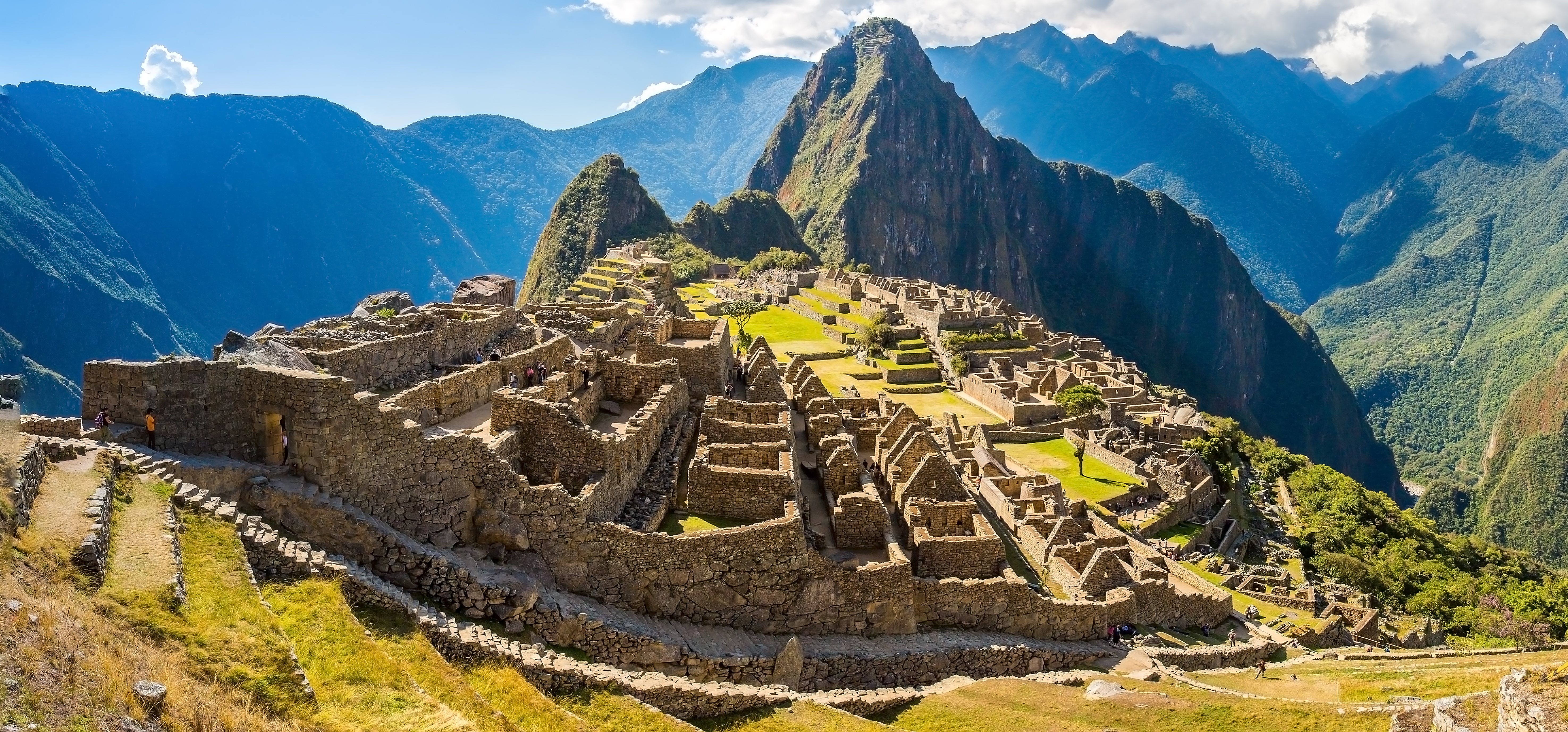 Image shows historic city of Machu Picchu with terraced city in foreground and mountain ranges in background