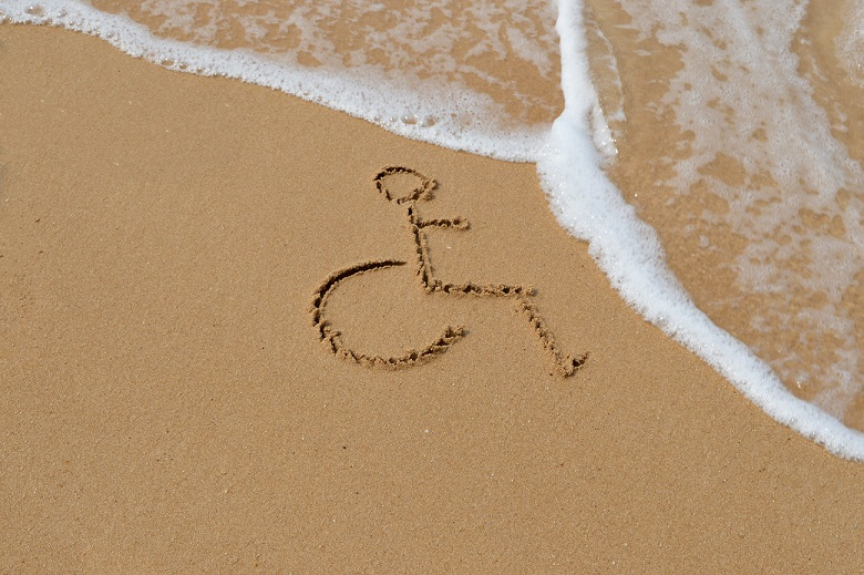 An outline of a wheelchair that has been drawn into the sand on a beach with water in the picture