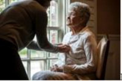 Older woman sits while being assisted to dress in an aged - care facility
