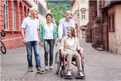 friends moving down a cobbled street. One person is a wheelchair user. All are smiling and talking.