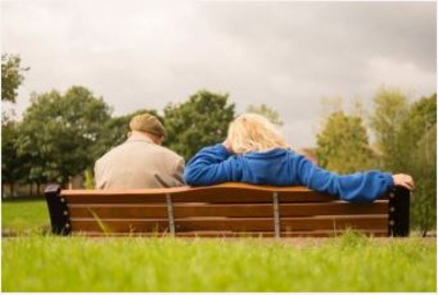 Two people sitting on a park bench, view from behind