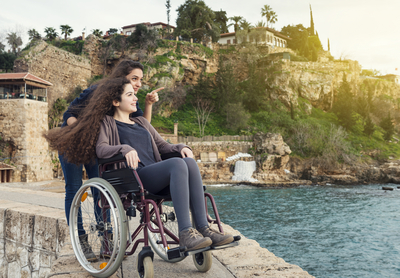A woman in a wheelchair and her companion looking and pointing at something
