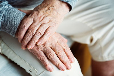 detail of older person holding hands in lap