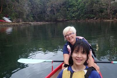 Two women sitting in a boat. Both are smiling and one is holding an oar.